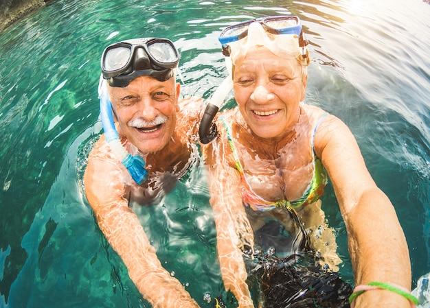 年配のカップルが楽しんで熱帯のビーチでシュノーケリング