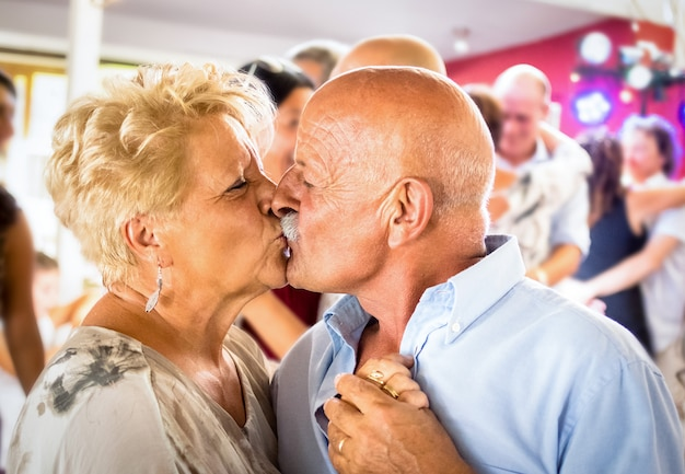 レストランの結婚式のお祝いパーティーでダンスを楽しんで幸せなシニア引退したカップル