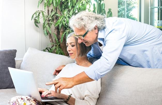 Пожилые пенсионеры, используя портативный компьютер у себя дома на диване
