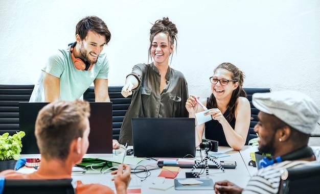 若者の従業員は、スタートアップスタジオでコンピューターと労働者をグループ化します。