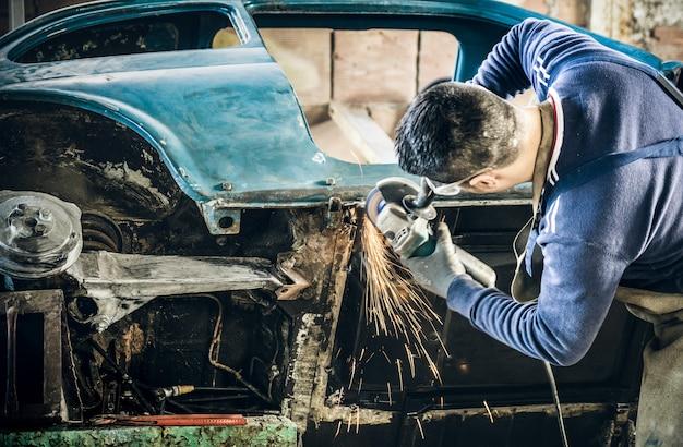 乱雑なガレージで電気グリッダーで古いビンテージ車のボディを修復する若い男機械労働者