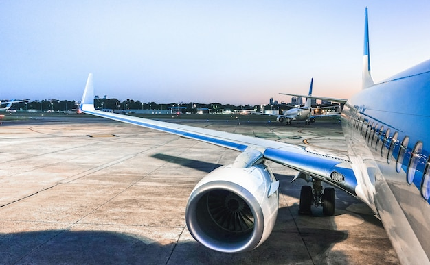 青の時間で離陸の準備ができている空港ターミナルゲートで飛行機