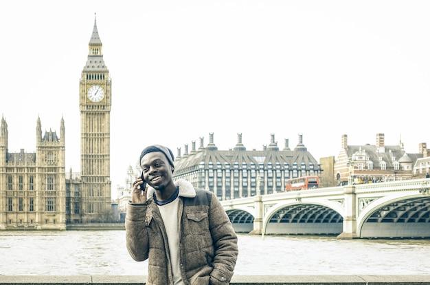 ロンドンのテムズ川岸でスマートフォンを使用して若い男