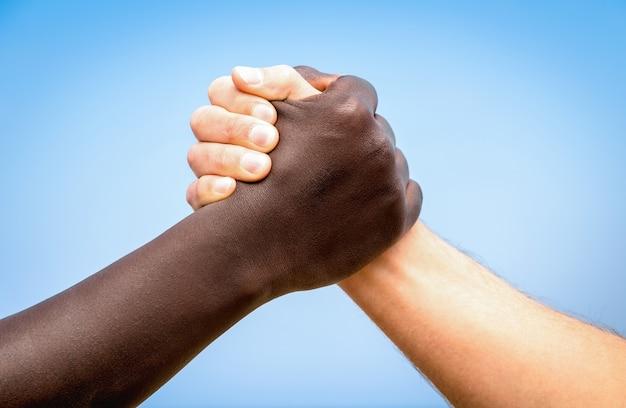 ハンドシェイクに黒と白の人間の手