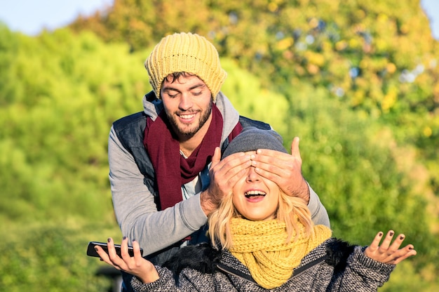 Счастливая пара влюбленных - красавец прикрывает глаза молодой удивленной девушкой
