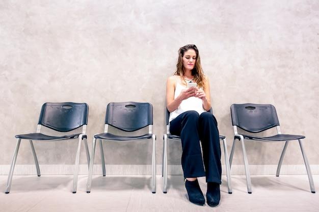 Задумчивая молодая женщина с мобильным смартфоном сидит в зале ожидания