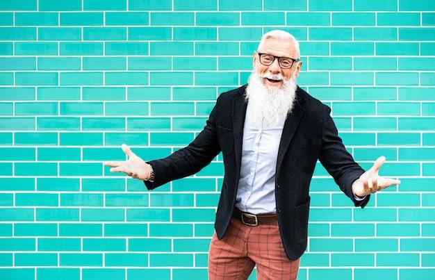 ターコイズブルーの壁を背景にポーズ歓迎気分で流行に敏感な男