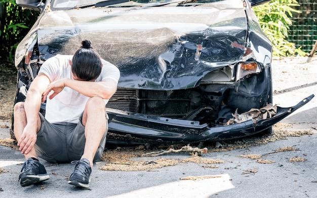 クラッシュ事故の後、古い破損した車で泣いている絶望的な男