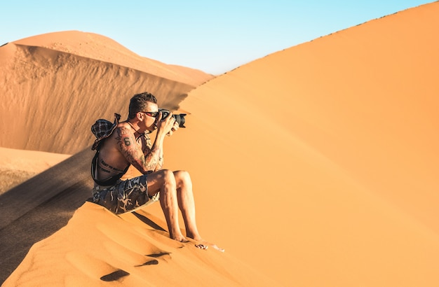 ナミビアのソーサスフライの砂丘で砂の上に座っている孤独な男写真家