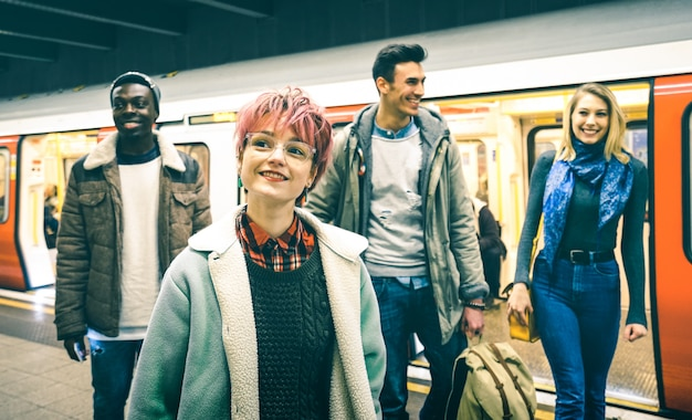 地下鉄地下鉄駅で歩いている多民族のヒップスターの友人グループ