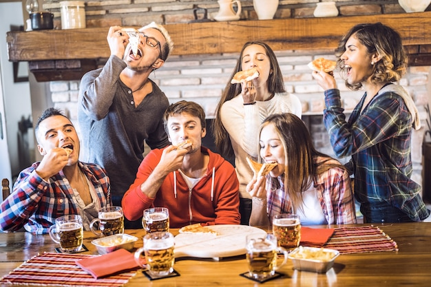 シャレーレストランの家でピザを食べて幸せな友人グループ
