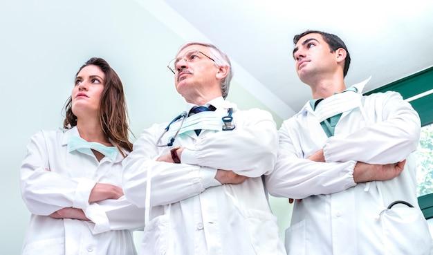 病院クリニックでコロナウイルスの大発生と戦う準備ができている若くて年長の医師