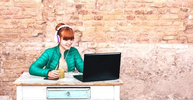 家のオフィスでラップトップを使用してヘッドフォンを持つ若い女