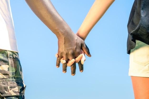 青い空を背景に手をつないで歩く多民族のカップル