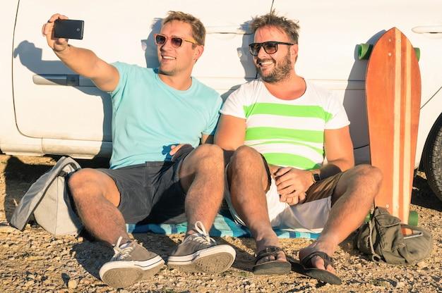 Счастливые друзья, делающие селфи в автомобильной поездке