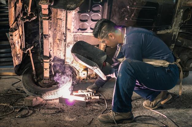 若い男メカニックワーカー乱雑なガレージで古いビンテージ車体を修復