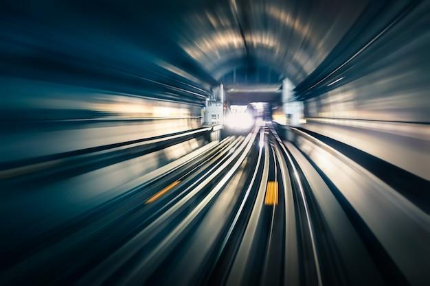 Туннель метрополитена с размытыми светлыми дорожками с прибывающим поездом в обратном направлении