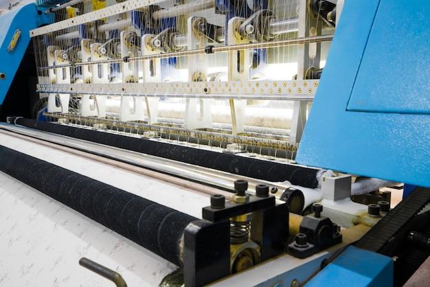 織物工場で織機、クローズアップ。工業用ファブリック生産ライン
