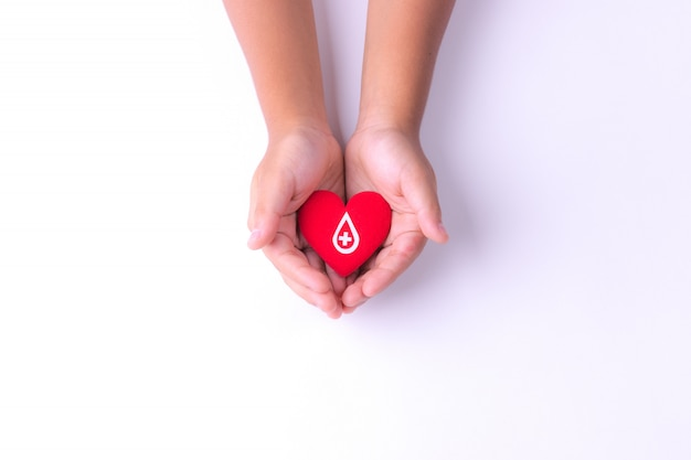 Ребенок руки держит красное сердце для сдачи крови