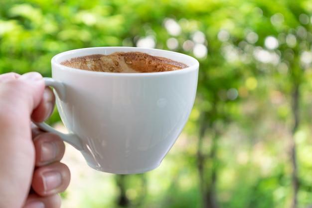 Рука крупного плана держа чашку кофе над естественной предпосылкой утра.