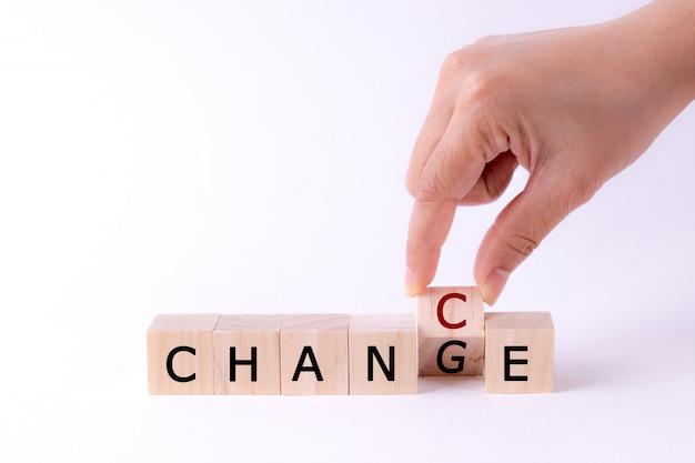 ブロックの上にフリップと木製のキューブを持っている手はチャンスに変更します。前向きな思考。