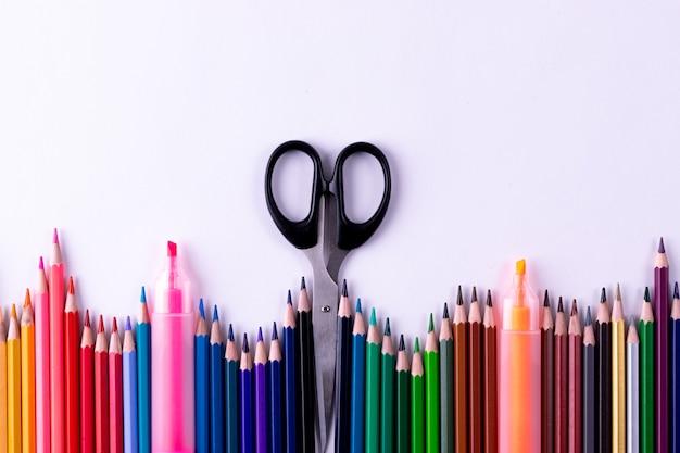 Цветные карандаши и канцелярские принадлежности на белом фоне таблицы. обратно в школу концепции.