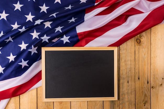 木製の背景に黒板とアメリカ合衆国の旗。米国の退役軍人、記念、独立と労働の日