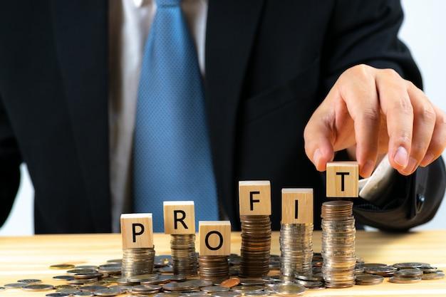 ビジネスマンは、テキストとコインスタックお金の上に木製の立方体を置く