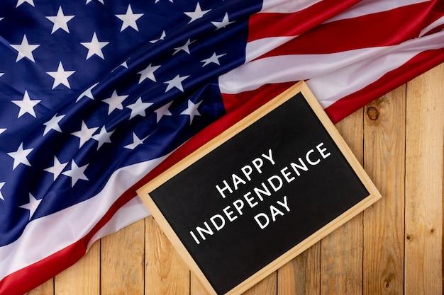 木製の背景に黒板とアメリカ合衆国の旗。