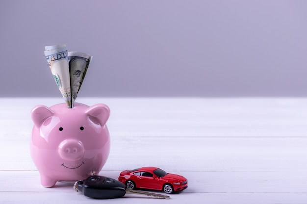 アメリカドル紙幣は貯金箱にお金を入れます。新しい車のためにお金を節約する。