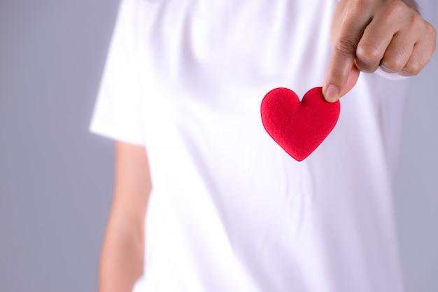 女性の手が世界の心の日の概念のための赤いハートを与える