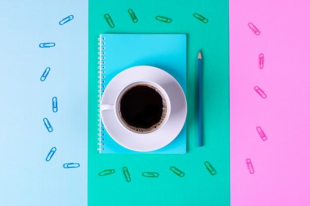 学校やオフィスのコンセプトに戻る。ブラックコーヒーとパステル調の青と緑のテーブルの上に鉛筆でノートブック。
