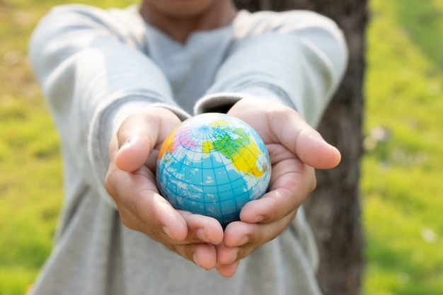 世界地球の日のコンセプトです。手は、自然の背景に地球のプラスチックを保持します。世界の概念を保存します。
