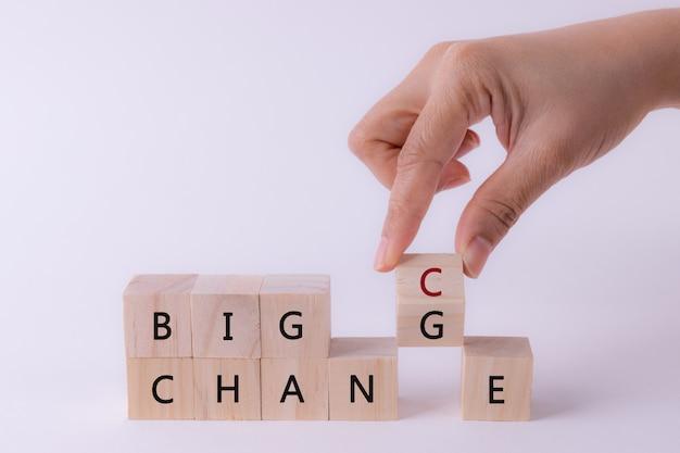 女性の手が大きなチャンスに大きな変化を持つ木製キューブを反転