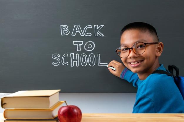 学校に戻る。少年は黒板にテキストを書き込みます