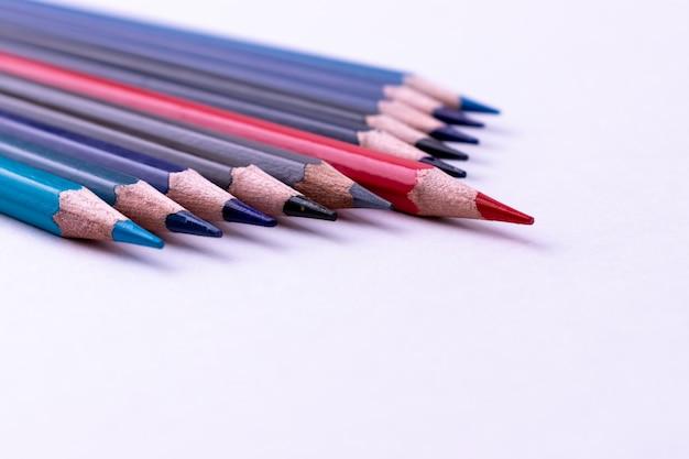 リーダーシップ、ビジネス成功のコンセプト。赤鉛筆は白い背景の上の他の鉛筆から目立つ。
