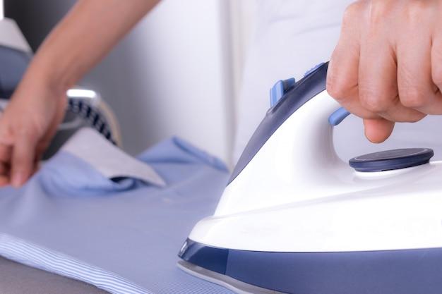 クローズアップ女性が自宅のランドリールームのアイロン台の上に服をアイロンします。