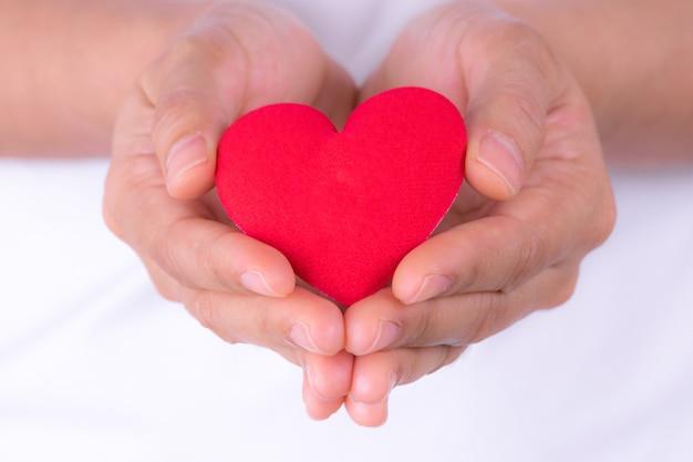 Женщина вручает держать красное сердце для дня сердца мира или концепции дня здоровья мира.