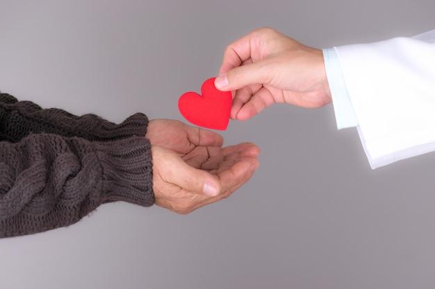 高齢患者に赤いハートを与える医師。世界の心の日。