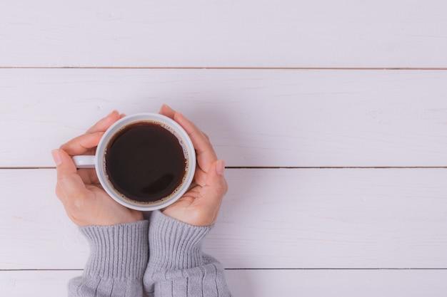 白い木製のテーブルに女性の手でコーヒーカップ。上面図。
