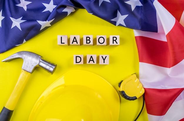 День труда сша концепция, набор различных инструментов на фоне желтой бумаги с флагом сша.