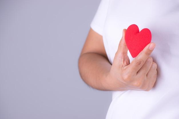 赤いハートを持つ女性の手。世界心臓の日コンセプト。