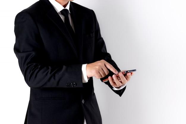 広告主のためのコピースペースと白い背景の上にスマートフォンを使用してビジネスの男性。