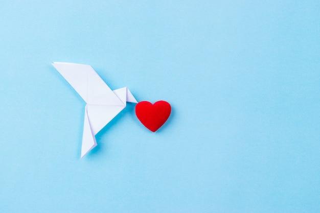 Белая птица из бумаги с красным сердцем. международный день мира.