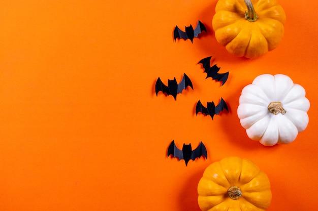 ハロウィーンのコンセプト。オレンジ色の紙の背景に黒い紙コウモリと新鮮なカボチャの群れ。