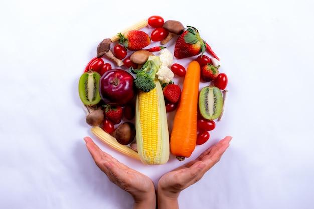 白い紙の上の新鮮な野菜や果物を持つ女性の手の平面図です。世界の食物の日またはベジタリアンの日。