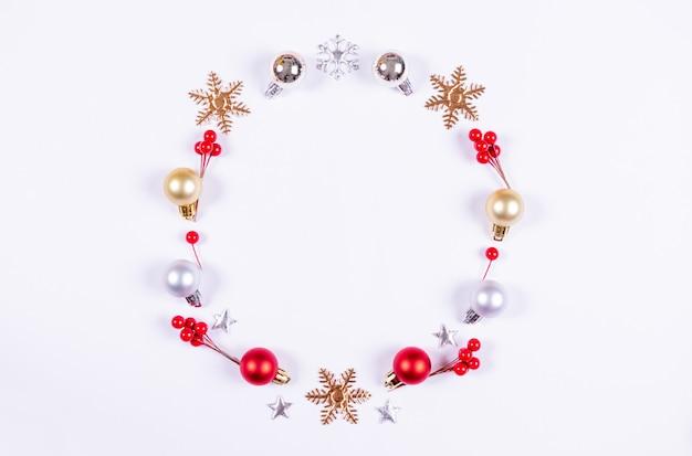 白い背景の赤い果実の装飾と装飾で作られたクリスマスリース。