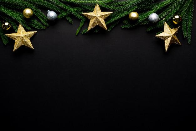 クリスマスの背景。モミの木の枝、黒の背景の星の装飾。フラット横たわっていた、トップビュー、コピースペース。