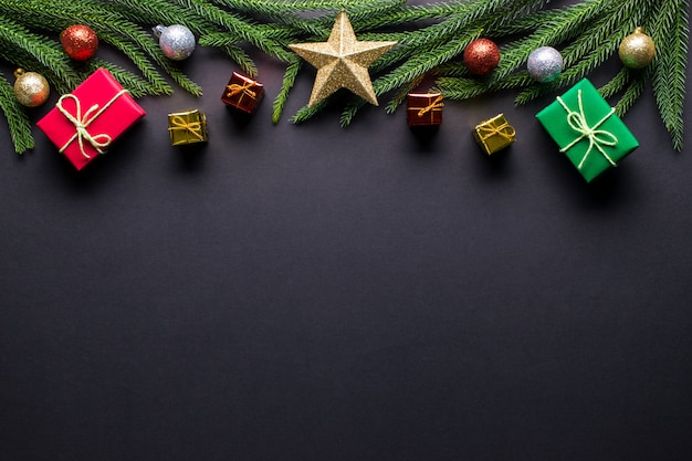 クリスマスの背景。ギフト、モミの木の枝、黒い背景にボールの装飾。フラット横たわっていた、トップビュー、コピースペース。