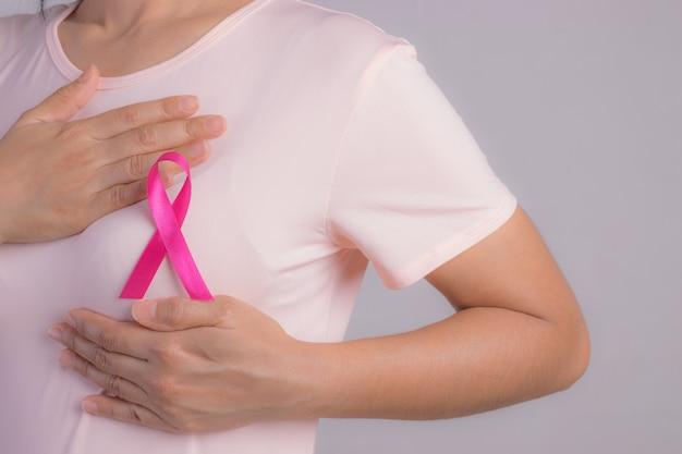 乳がんの原因をサポートする女性の胸にピンクのバッジリボンのクローズアップ